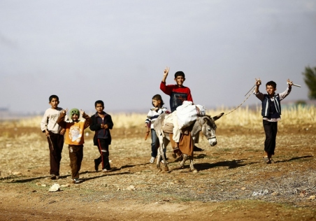 Kurdish refugee boys from the Syrian town of Kobani flash victory signs as they walk near in the southeastern town of Suruc on the Turkish-Syrian border
